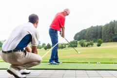 Spielen Sie den Trainer Golf, der mit Golfspieler auf Driving-Range arbeitet Stockbild