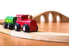 Spielen Sie den Zug, der vom Holz mit Brücke im Hintergrund hergestellt wird Stockfotografie