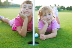Spielen Sie die Schwestermädchen golf, die grüne Lochkugel legend entspannt werden Stockfotografie