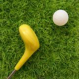 Spielen Sie einen Golfball mit einem gelben Stock auf dem Hintergrund grünen g stockbilder