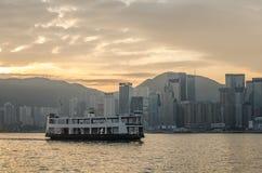 Spielen Sie Fähre in Victoria Harbor- und HK-Skylinen bei Sonnenaufgang die Hauptrolle Ansicht von Kowloon auf Hong Kong Lizenzfreie Stockfotos