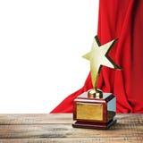 Spielen Sie hölzerne Tabelle des Preises und auf dem Hintergrund des roten Trennvorhangs die Hauptrolle Stockfotografie