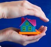 Spielen Sie Haus in den menschlichen Händen - ein Symbol des Schutzes Stockbild
