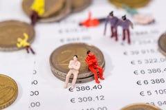 spielen Sie Leute mit Euromünzen- und Geschäftsdiagramm Stockbilder