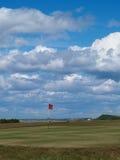 Spielen Sie Markierungsfahne auf dem Grün an einem Küstekurs Golf Stockfotos