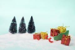 Spielen Sie Pferdeschlitten und Geschenkboxen auf süßes veintage Grün hellem turquoi Stockbild