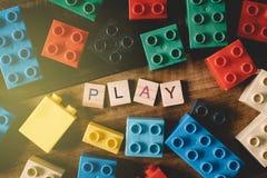 Spielen Sie Plastikziegelstein mit Alphabetfliesenwort SPIEL auf Holztisch Stockfotos