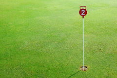 Spielen Sie Praxisübungsgrünloch und markiert mit einem roten Zeichen Golf lizenzfreie stockfotografie