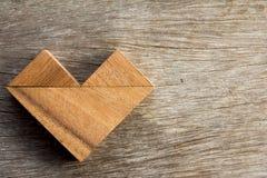 Spielen Sie Puzzlespiel in der Herzform auf hölzernem Hintergrund Lizenzfreies Stockbild
