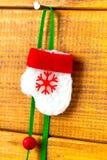 Spielen Sie roten Weihnachtshandschuh mit Schneeflocken auf einem Nagelhintergrund von hölzernen Brettern Lizenzfreie Stockbilder