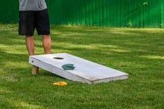 Spielen von cornhole Spiel an einem sonnigen Tag im Hinterhof Lizenzfreie Stockfotos