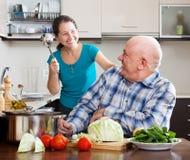 Spielen von den reifen Paaren, die Lebensmittel kochen lizenzfreie stockfotos