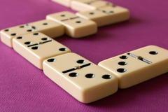 Spielen von Dominos auf einem purpurroten Hintergrund Das Konzept des gam lizenzfreie stockfotos