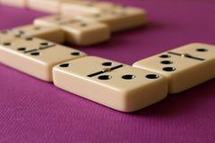 Spielen von Dominos auf einem purpurroten Hintergrund Das Konzept des gam lizenzfreies stockfoto