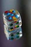 Spielen von Würfeln im transparenten Harz und in den mehrfarbigen Zahlen Stockbild