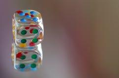 Spielen von Würfeln im transparenten Harz und in den mehrfarbigen Zahlen Stockbilder