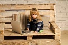 Spielende Kinder - glückliches Spiel Kleiner Junge, der auf Bank, on-line-Kauf blogging ist Lizenzfreie Stockfotos