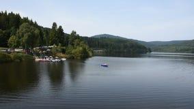Spielende Leute und Paddelboot im Schwarzenbachtalsperre See im Schwarzwald stock video