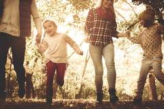 Spielende und laufende Abflussrinne der glücklichen Familie parken zusammen lizenzfreie stockfotos