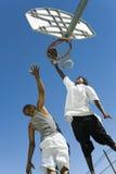 Spieler, der andere schützt, wie er Basketball schießt Lizenzfreie Stockfotos