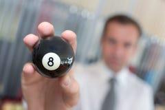 Spieler, der billard 8 Ball hält Lizenzfreie Stockfotos