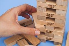 Spieler, der Block von Jenga-Turm konstruiert entfernt Lizenzfreie Stockfotos
