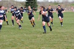 Spieler, der mit Kugel in der Rugby-Abgleichung der Frauen läuft Lizenzfreies Stockbild