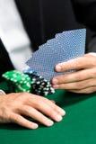 Spieler, der Schürhakenkarten mit Chips auf der Tabelle spielt Stockbilder