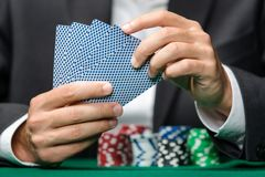 Spieler, der Schürhakenkarten mit Pokerchips auf der Tabelle spielt Stockbild