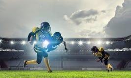 Spieler des amerikanischen Fußballs an der Arena Gemischte Medien lizenzfreie stockfotografie