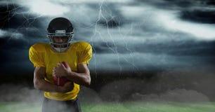 Spieler des amerikanischen Fußballs, der auf dem Feld mit Blitz steht Stockfotografie
