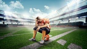 Spieler des amerikanischen Fußballs, der auf Sturzhelm im Stadion sitzt Stockfotografie