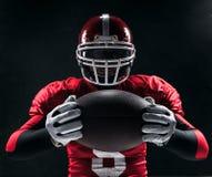 Spieler des amerikanischen Fußballs, der mit Ball auf schwarzem Hintergrund aufwirft Stockfoto