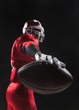 Spieler des amerikanischen Fußballs, der mit Ball auf schwarzem Hintergrund aufwirft Stockbild