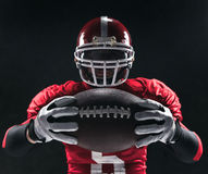 Spieler des amerikanischen Fußballs, der mit Ball auf schwarzem Hintergrund aufwirft Lizenzfreies Stockfoto