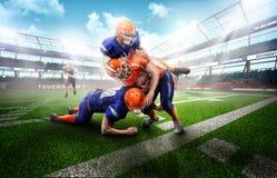 Spieler des amerikanischen Fußballs des Angriffs auf Gras im Stadion Stockbild