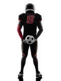 Spieler des amerikanischen Fußballs, der Fußballschattenbild hält Stockfotografie