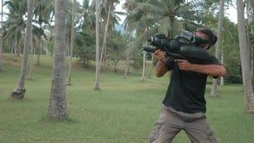 Spieler im Kopfhörer der virtuellen Realität mit Waffe im Dschungel, der in Zeitlupe läuft stock footage