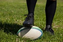 Spieler mit dem Bein auf Rugbyball Lizenzfreies Stockfoto
