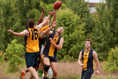 Spieler springen, um Ball im Australier-Regel-Fußballspiel zu fangen Lizenzfreies Stockbild