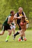 Spieler vermeidet, im Amateuraustralier-Regel-Fußballspiel angepackt zu werden Stockfotos