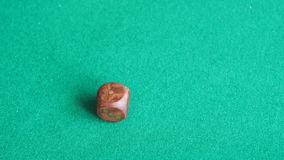 Spieler wirft einen hölzernen Würfel zweimal auf grünem Brett stock video footage