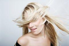 Spielerische blonde Frau, die ihr Haar schlägt Stockbilder
