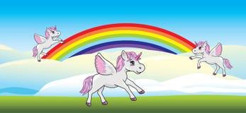 Spielerische Einhörner auf einem Regenbogen Lizenzfreies Stockfoto