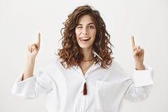 Spielerische entzückende kaukasische Frau mit dem gelockten Haar oben zeigend mit beiden Zeigefingern, Zunge und das Lächeln hera Stockfotos