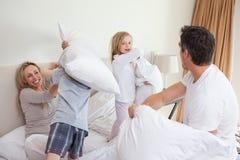 Spielerische Familie, die einen Kissenkampf hat Stockbild