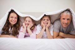 Spielerische Familie, die unter einem Duvet liegt stockbilder