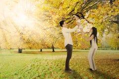 Spielerische Familie unter Herbstbaum Stockfoto