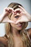 Spielerische Frau, die eine Herzgeste macht Lizenzfreie Stockbilder