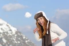 Spielerische Frau, die einen Schneeball im Winter an den Feiertagen wirft Lizenzfreies Stockbild